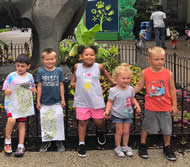 Small kids standing together in front of a garden