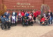 People in wheelchairs in front of wall filled with plaques